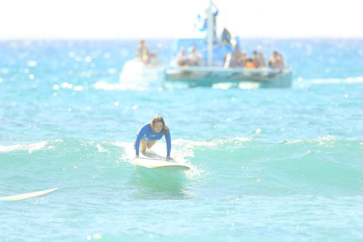 Me riding a wave during my surfing lesson at Waikiki Beach in Oahu, Hawaii