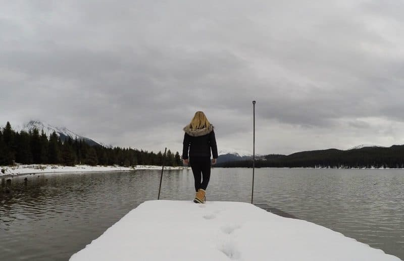 Standing on the snow covered docks of Maligne Lake, in Jasper, Alberta