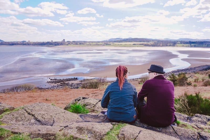 Friends enjoy the view of Cramond beach from the island