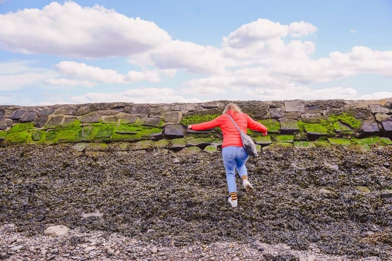 Woman in red jacket walking up the causeway at Cramond Island