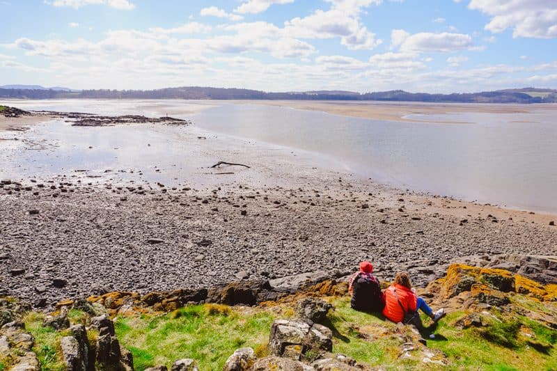 Two girls having a picnic on the grass at Cramond Island in Edinburgh