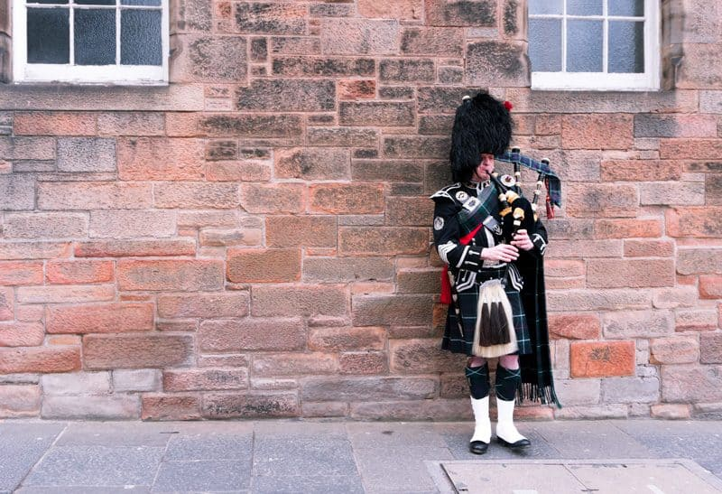 A Scottish bagpiper performs on the Royal Mile