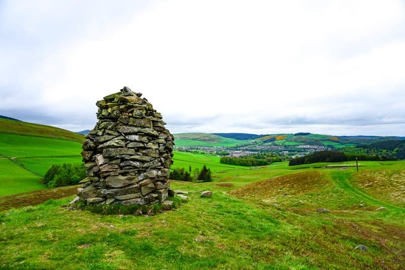 Cairn in the Traquair Hills looking back to Galashiels on the Scottish National Trail